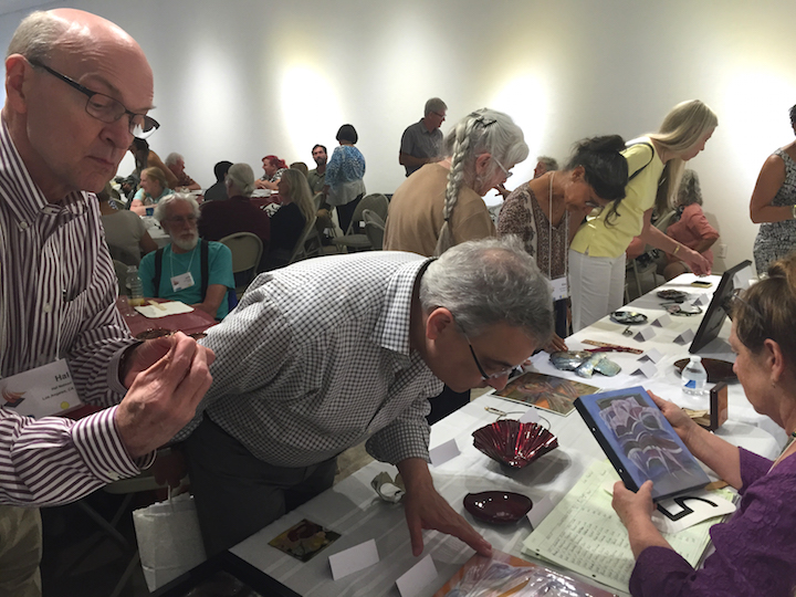 Hal Nelson, Jazzar Bernard and others looking at pieces for bid at the live auction